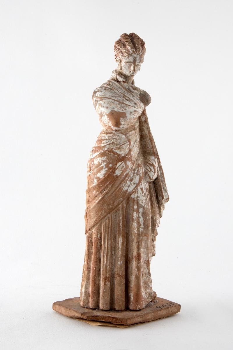 Figurin i uglasert terrakotta, dekorert med hvit begitning. Figurinen er formet som en stående kvinne, iført himation. Rektangulær åpning i ryggen, og innsiden er hul. Figuren står på en fotplate av terrakotta.