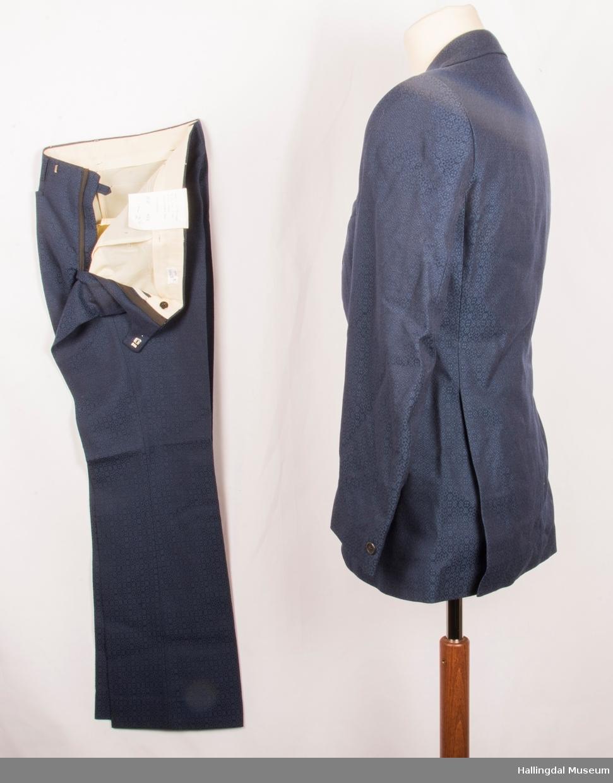 Kavaler herredress, jakke og bukse i mørkt blått tøy med smått mønster. Svart syntetisk silkefor. Jakka har skulderputer, klaff på lommene, 2 splitt er bak og store slag på kragen.  Den er knept med 2 knapper midt framme.  1 pynteknapp på hvert erme. Buksa har har antydning til sleng.