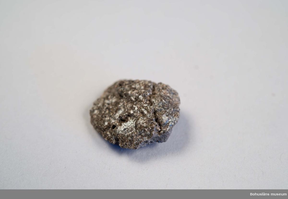 Degel, fragmentarisk. Förmodligen del av s k sluten degel. Hårt bränd, bitvis sintrad grönaktig glasartad yta.  Dessa deglar användes för finsmide i guld och silver under sen järnålder-vikingatid. För motsvarande föremål se UM029674:01A.  Landskap BOHUSLÄN