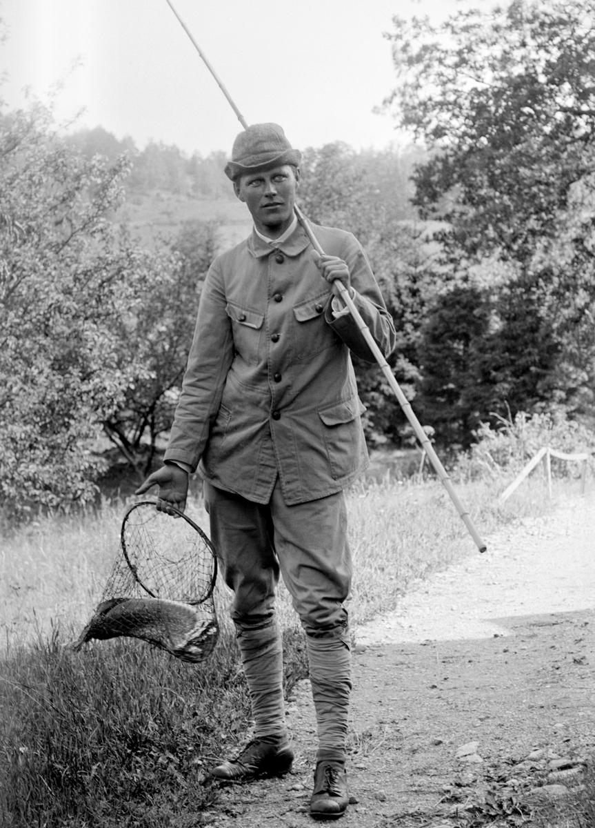 En präktig gädda blev det för Sigurd Hallin denna soliga sommardag 1918. Här är han precis hemkommen till morbrodern Emil Durling i Strömmen som passar på att föreviga tillfället.
