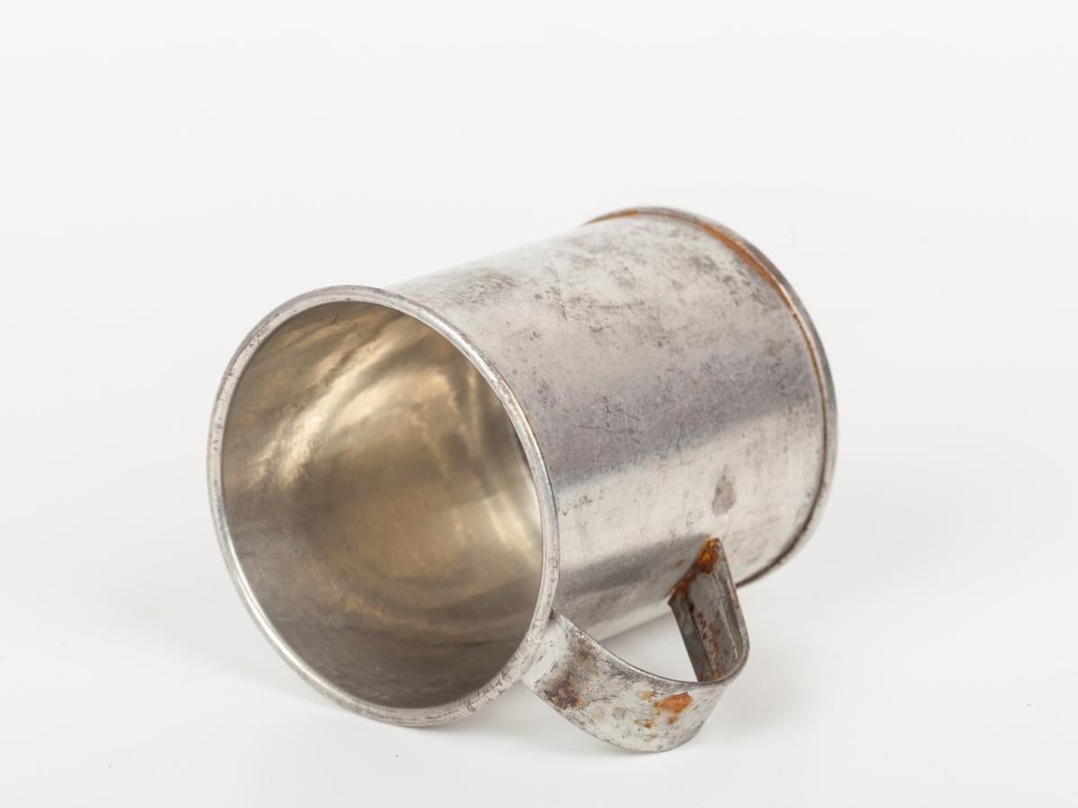 """Målet ser ut som en """"avstumpet"""", rund blikkboks med nedtrukket kant hvor det er loddet en hank i topp og bunn. Det finnes ikke noe angitt mål. Full kopp er 1 dl."""