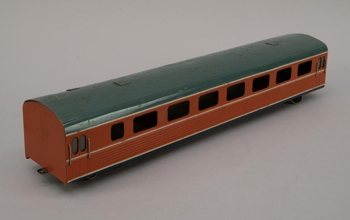 Modell i skala 1:50 av motorvagn UBoa2, X9M. Mellanvagn. Orange med vita linjer och grågrönt tak.
