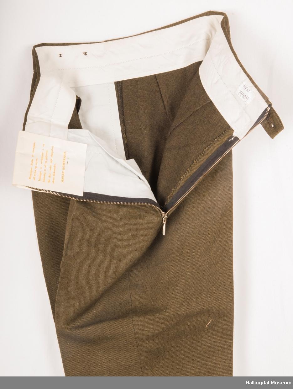 Brun smal ullbukse med metallglidelås i venstre side.  To lommer, ingen baklommer.  Spensel inni linningen til strammig av livvidden.