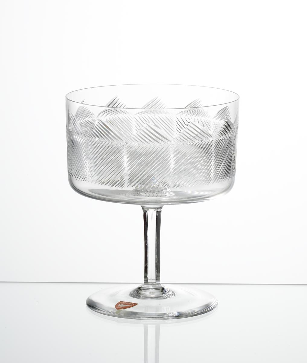 Champagneskål, cylindrisk kupa med skärslipade diagonala linjer som skapar ett geometriskt mönster. Fasettslipat ben och slät fot.
