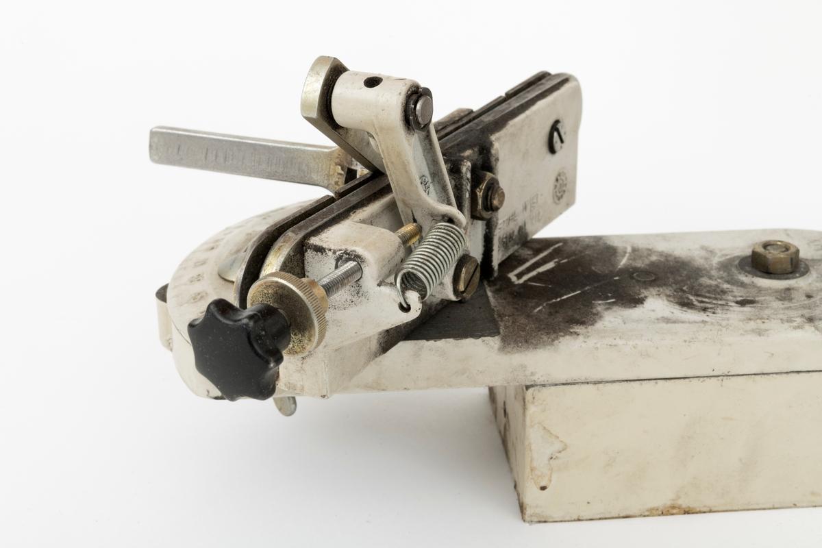 Elektrisk slipemaskin, smergelskive, benkslipemaskin, med en skive brukt til sliping av kjeder til motorsager og hogtsmaskinaggregater ved skogskolen på Sønsterud i Åsnes kommune. For registrator ser det ut til at slipemaskinens komponenter hovedsakelig er utført i presstøpt metall.    Slipemaskienen består av tre hovedkomponeneter: en ramme (brakett, sokkel), motorhus med slipeskive og holder for sagkjede. Braketten, som består av en fot og en del som er vertikalt montert til foten (sokkelen), kan festes både i vegg og til arbeidsbenk. Holderen for kjedet og motoren som driver slipeskiva er begge festet til braketten (ramma). Kjedeholderen er festet til foten, mens motoren som driver slieskiva er montert til den vertikale delen av braketten.  I rammas fot er det utfrest et spor, en slisse som gjør det mulig å bevge kjedeholderen. På ene siden av foten, sokkelen, er det en linjal som har en skala fra -40 til + 40. Kjedeholderen kan stilles inn på ulike avstander langs denne skalaen. Klemma, holderen for kjedet, er utstyrt med ei beveglig gradskive som gjør det mulig å vinkle kjedeholderen i forhold til slipeskiva. Den elektriske motoren er fastmontert med en gjennomgående mutterskrue i braketten, en aksling som gjør slipeskiva og elektromotoren beveglig. På elektromotoren er det montert et håndtak med en kule i hardplats, som gjør det lettere å trykke slipeskiva inn mot sagkjedet. En skrue med ratt i hardplast har en stopperfunksjon for slipeskiva, slik at avstanden mellom kjedet og skiva er lik under hele slipeprosessen.   Like over slipeskivas beskyttelsesdeksel er det påklistret et merke som viser at en skal ha på vernebriller når en bruker slipemaskinen.