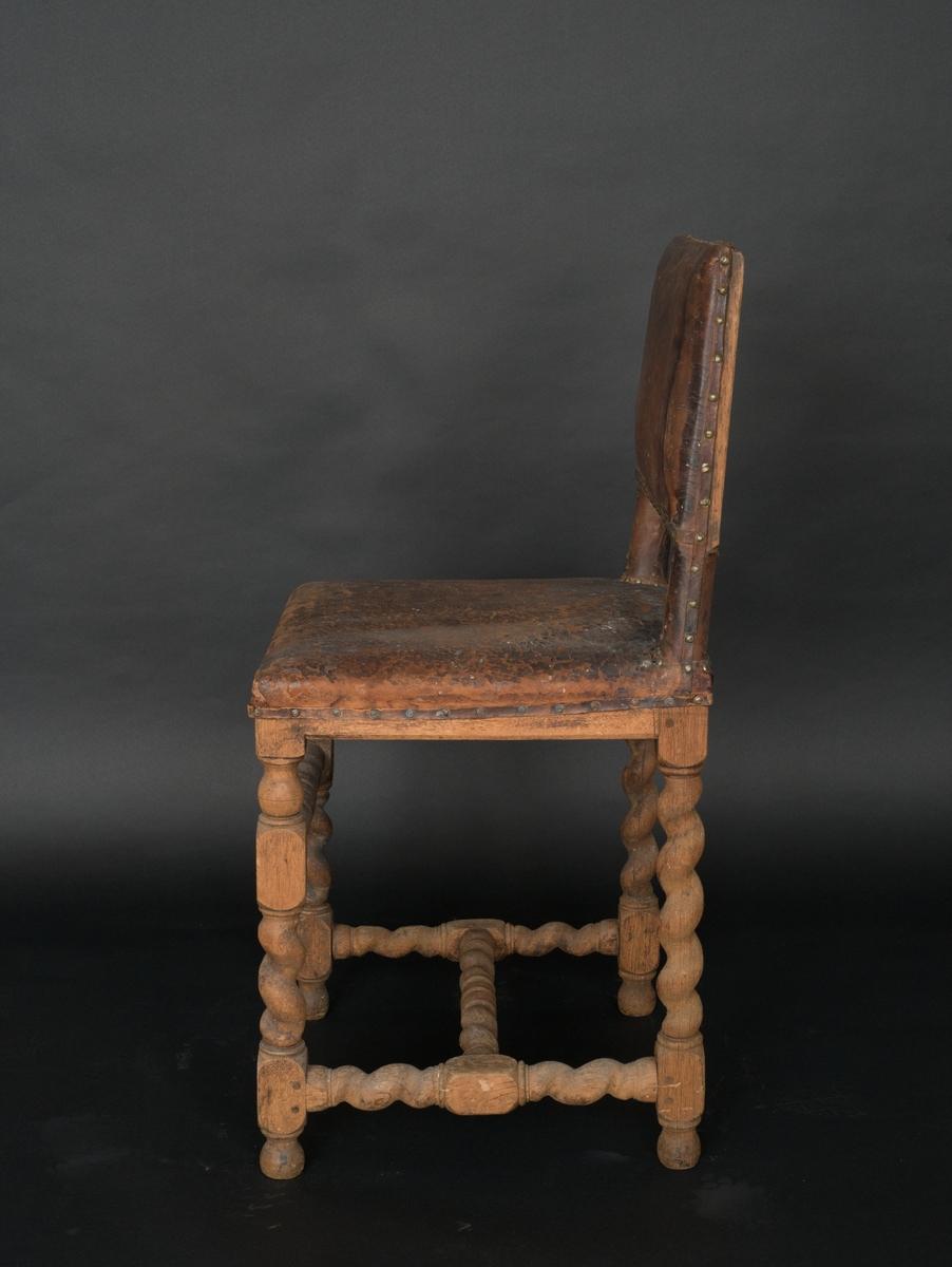 Stol av ek med spiralvridna ben och kryss. Samt läderklädsel. Rakt överstycke och ryggslå. Mellan ryggstolparna är ryggbrickan, något bakåtlutande, stoppad och klädd med läder som är fastsatt med mässingsnitar. På samma sätt är sitsen gjord, fästad i sargen. Även ryggstolparnas del ovan sitsen är klädda med läder och fastnitade med mässingsstift. Sargen har en liten profilering. Nedtill finns ett H-format kryss mellan benen. Mellan frambenen finns även en tvärslå lite högre upp.