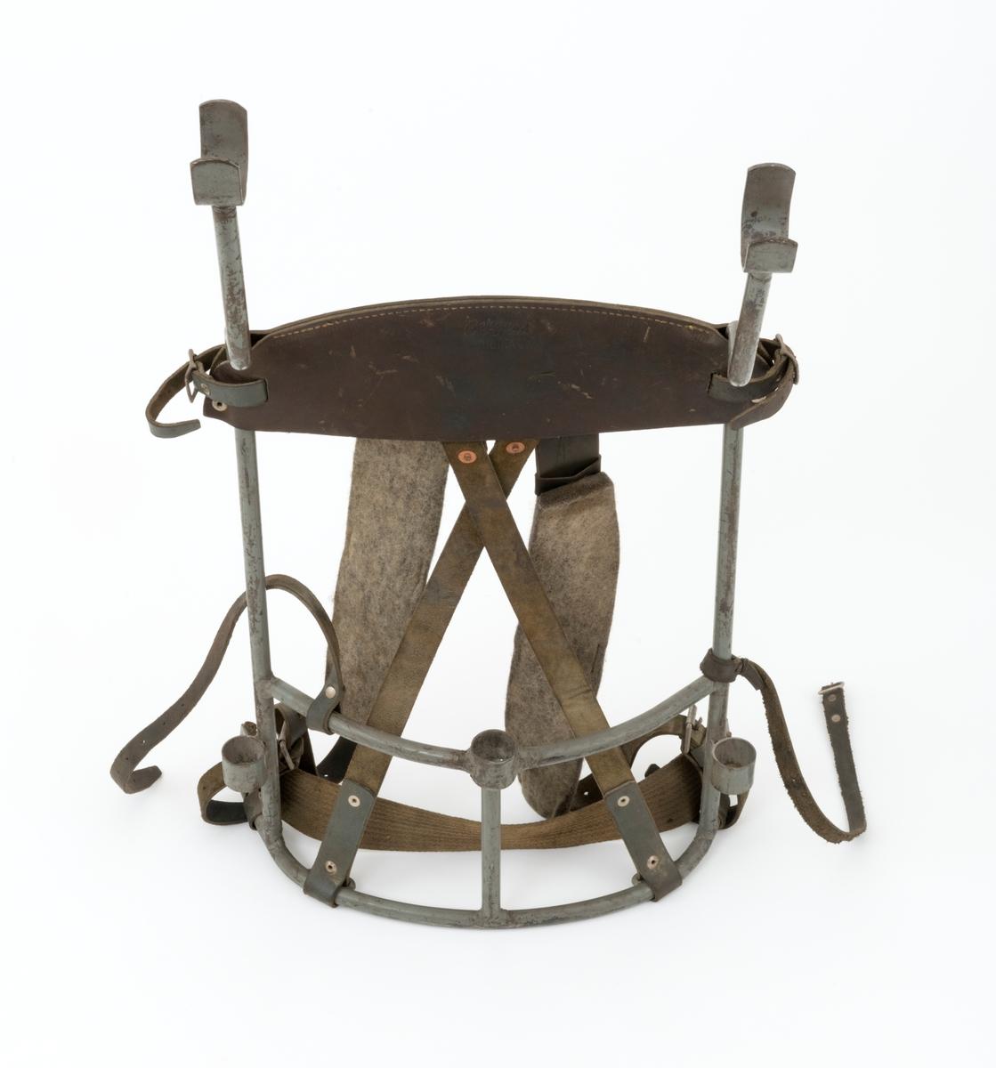 """Bæremeis for bæring av motordrevet bergbormaskin på ryggen. Bæremeisen er laget av en stålrørsramme med bærereimer (seler, feslinger) og støttereimer i lær. Bæreselene, feslingene, er regulerbare med hjelp av metallspenner. Selene (feslingene) er polstret med ullfilt. Den rektangulære stålrørramma består av to vertkalt stående stålrør på hver side med en bøy øverst. I enden av denne bøyen er det påsveiset klyper. Registrator antar at bormaskinenes styre senkes ned i disse klypene. Ramma får videre sin form ved at det mellom de vertikalt stående rørene er påsveiset tre horisontalt liggende rør, i overkant av 30 centiemter lange. To av rørene er svakt krummende for å gi passform rundt brukeresn rygg, mens det øverste røret buer svakt oppover på midten.  Det øverste røret, som blir liggende an mot brukerens skulderparti, er polstret med et lærstykke, som på grunn av rørets form også buer svakt oppover. Lærstykket, som er dobbelt, er sydd i overkant og naglet med to nagler på hver side nede. På hver side av lærstykket er det utskåret spalter. Gjennom disse spaltene er det tredd lærreimer med spenner. Bæreselene, feslingene, er tredd over det øverste tverrgående røret i ramma. Nederst på de langsgående stålrrørene, er det påsvesiet """"ører"""" for innfesting av bæreselenes regulerbare reimer. I dsse ørene er det også fastnaglet et bånd, antakelig et lerretbånd, som omslutter brukerens ryggparti. Det er også fastmontert to lærreimer, cirka 40 centimeter lange, på stålrørsramma. Den ene reima, som er utstyrt med en metallspenne, er festet til det langsgånde stålrøret med en tynn ståltråd. Den andre reima er festet til det midtre tverrgående stålrøret med en metallnagle. Registrator antar at disse reimene tres rundt bormaskinen og sammenkobles med metallspennen for å holde maskinen stabil i bæremeisen."""