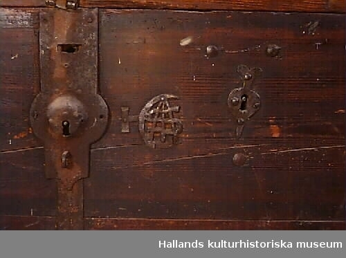 """Kista med kraftiga beslag. I hörnen heltäckande beslag med nitar. I sidorna av locket likadant. Mitt över locket band med nitar. Mitt fram dubbelt lås. Ett vanligt lås och över det en kläpp för hänglås. Bottenbeslag. På framsidan smitt monogram """"168 """" där sista siffran saknas (enligt kapselkort 1689) och lås med låsskylt. På höger sida lås med låsskylt och monogram med smidda bokstäver """"HCAS"""" (enligt kapselkort G.A.S.). Nu modernt hänglås"""