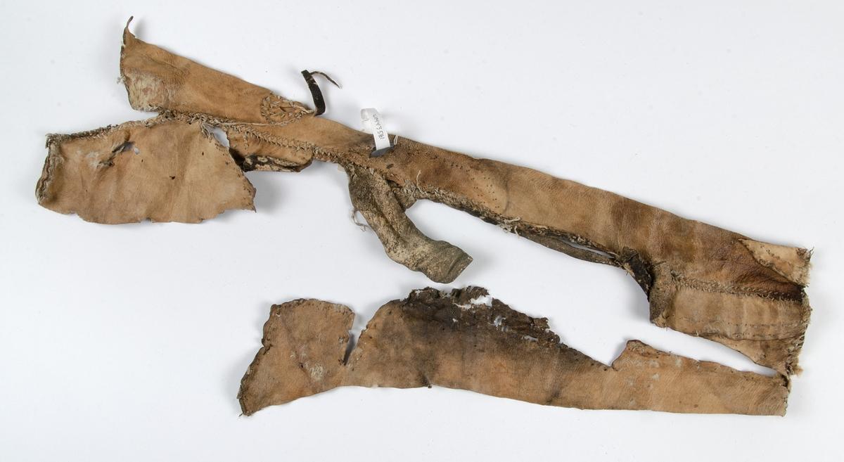 Fragment av pälsplagg. Möjligen sida av plagg. (väst, tröja), Handsydd med lintråd, efterstygn och snedställda stygn. Lite pälsrester kvar.