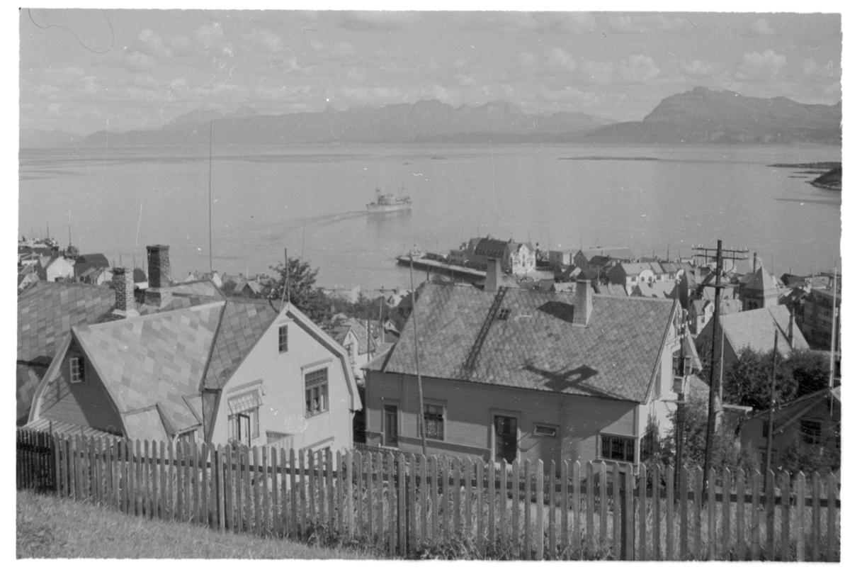 """Bebyggelse i Harstad, fotografert fra Jørns gate på Eineberget. I bakgrunnen ser vi M/S """"Bretagne"""" som bakker ut fra dampskipskaia."""