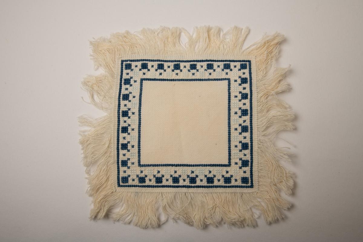 Brikke med korsstingsbroderi. Firkantet  brikke med bord langs kanten i hvitt og dypblått. Tre cm. lange frynser langs kantene,