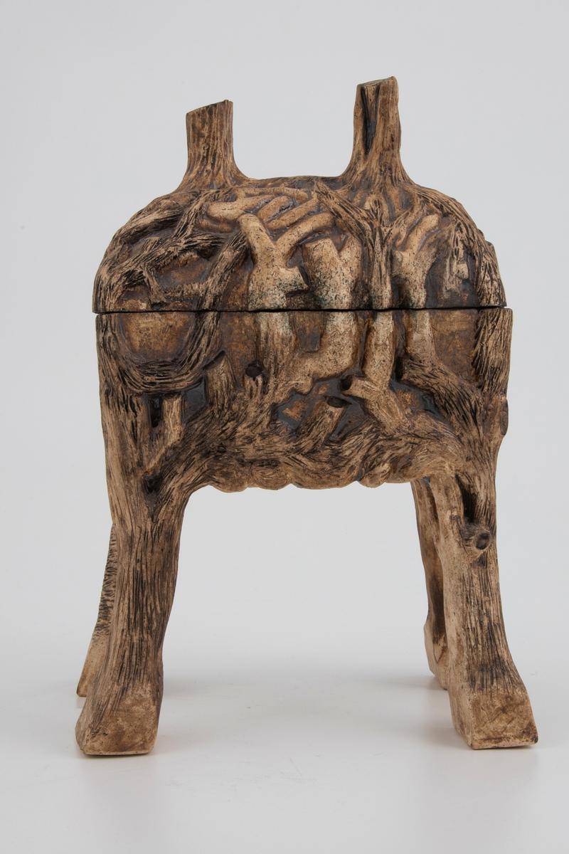 Naturinspirert dekor i relieff som ligner trerøtter. Røttene sprer seg naturlig nedover skrinet fra lokkets håndtak som ligner to trestammer. Dekoren har graveringer som gir den et naturlastisk og organisk preg.