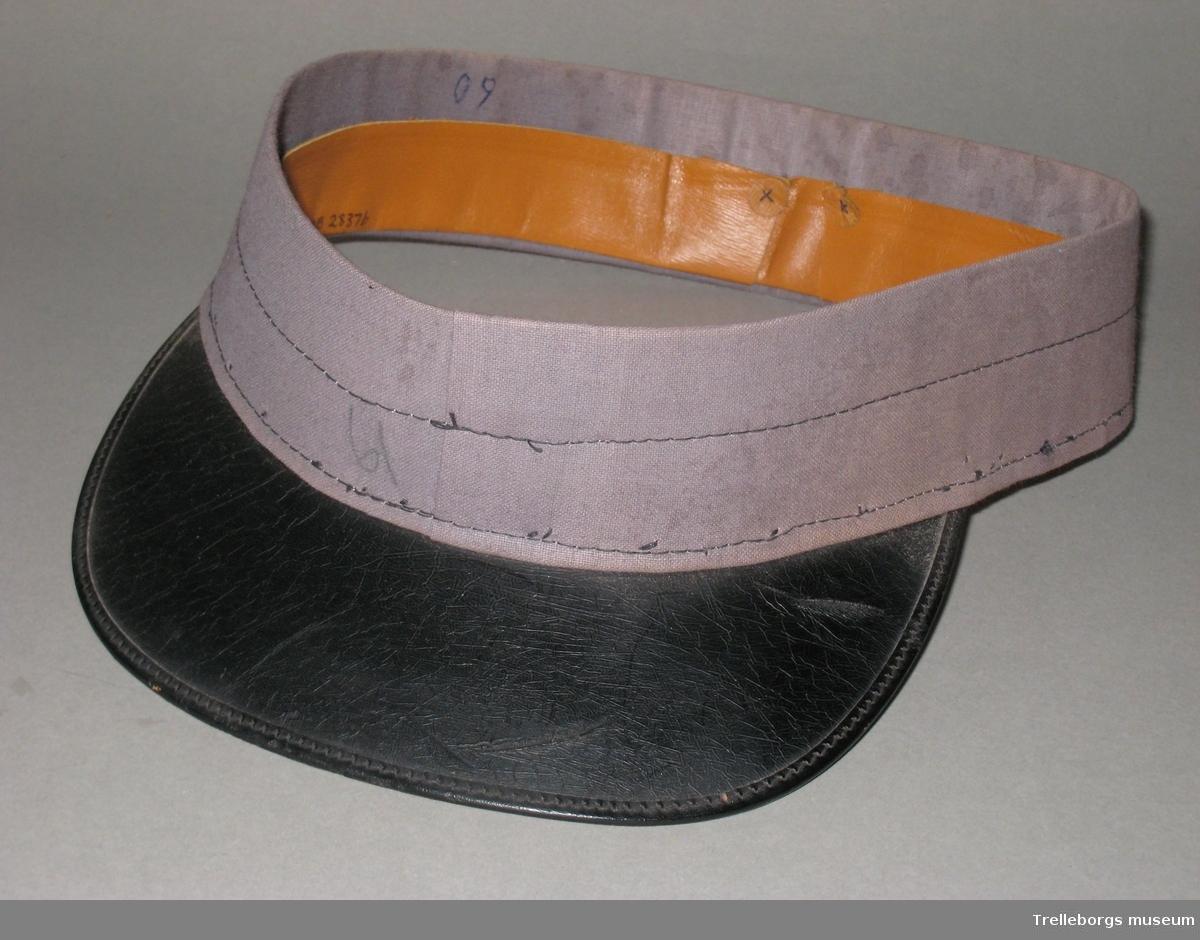 a: Pappstome till keps, klädd i grått tyg. Insidan klädd med skinnband. Skärm i svart filt och band med mönster längs kanten. En svar plastknapp på var sida om  skärmen. Knapparna har reliefdekor i form av ett ankare.  b: Pappstome till keps, klädd i grått tyg. Insidan klädd med skinnband. Bred skärm i svart, plastliknande material. Skärmen är grön på undersidan.  c: Pappstome till keps, klädd i grått tyg. Insidan klädd med skinnband. Smal skärm i svart, plastliknande material.