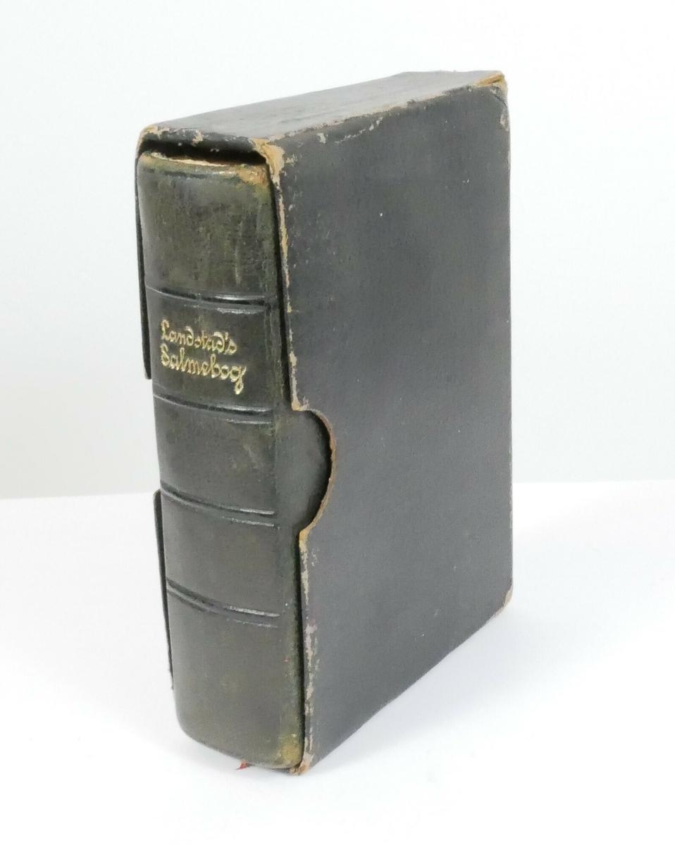 Rektangulær salmebok i svart skinn med forgylte sider. Boken ligger i en rektangulær beholder av svart kartong.