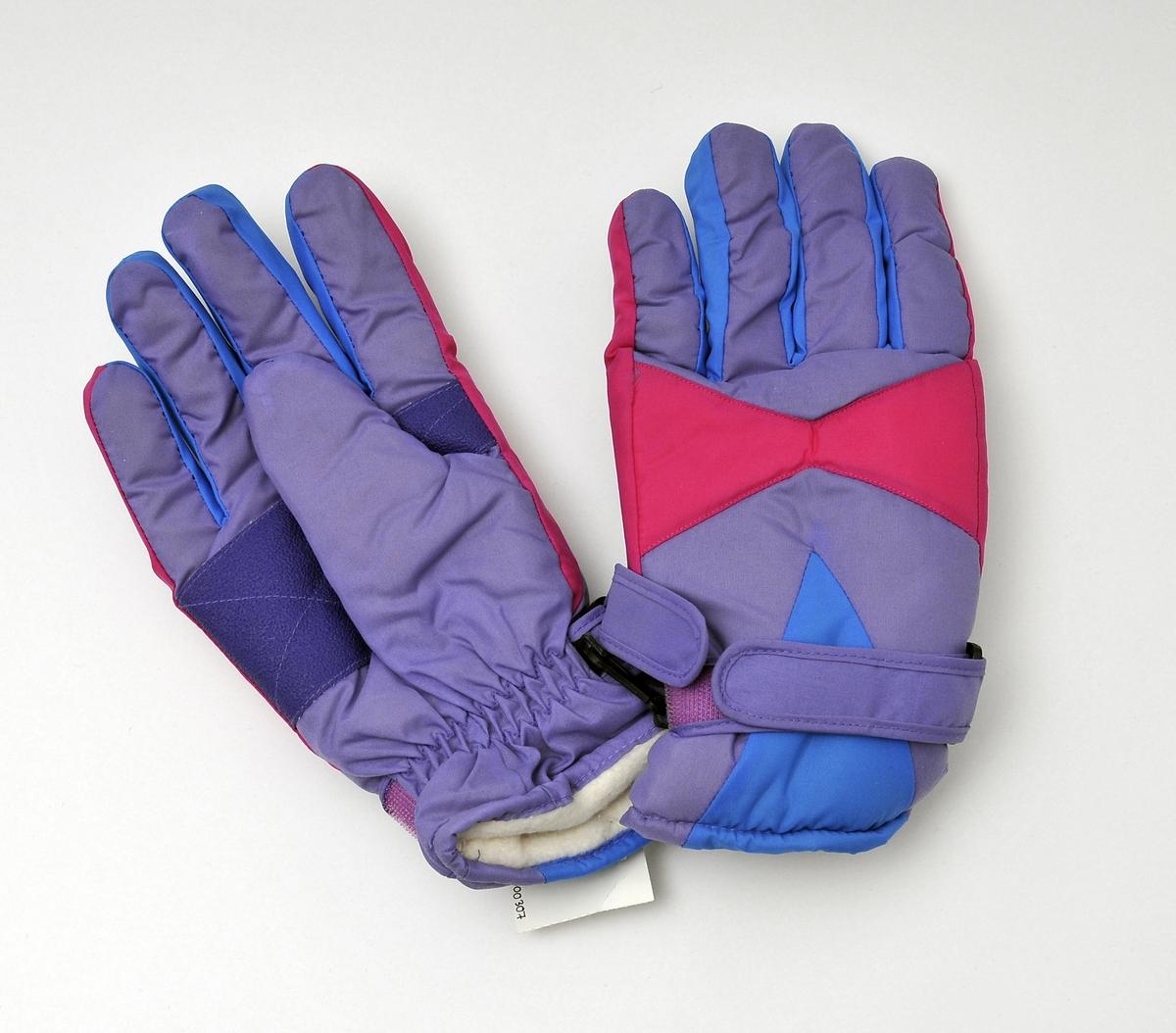 Et par lilla, blå og cerise skihansker for ungdom. gummiert flate inni handa, for bedre grep. Borrelås rundt handleddet, for å kunne stramme.