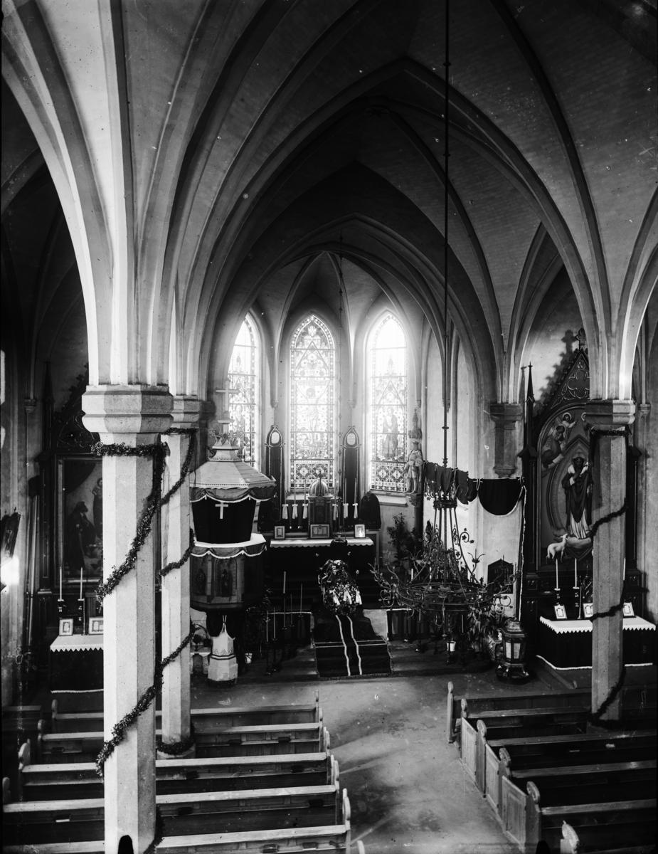Kirkeinteriør i ukjent kirke. Begravelseskiste på alteret.