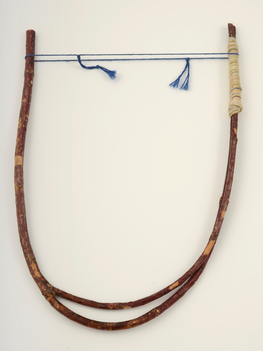 Halssmykke bestående av en gren som deler seg i to. Grenen er bøyd i hesteskoform ved hjelp av tynt, blått bomullsgarn med to dusker. Rundt den dobbelte delen av grenen er det surret garn i forskjellige pastellfarger i et cirka 6 cm langt stykke.