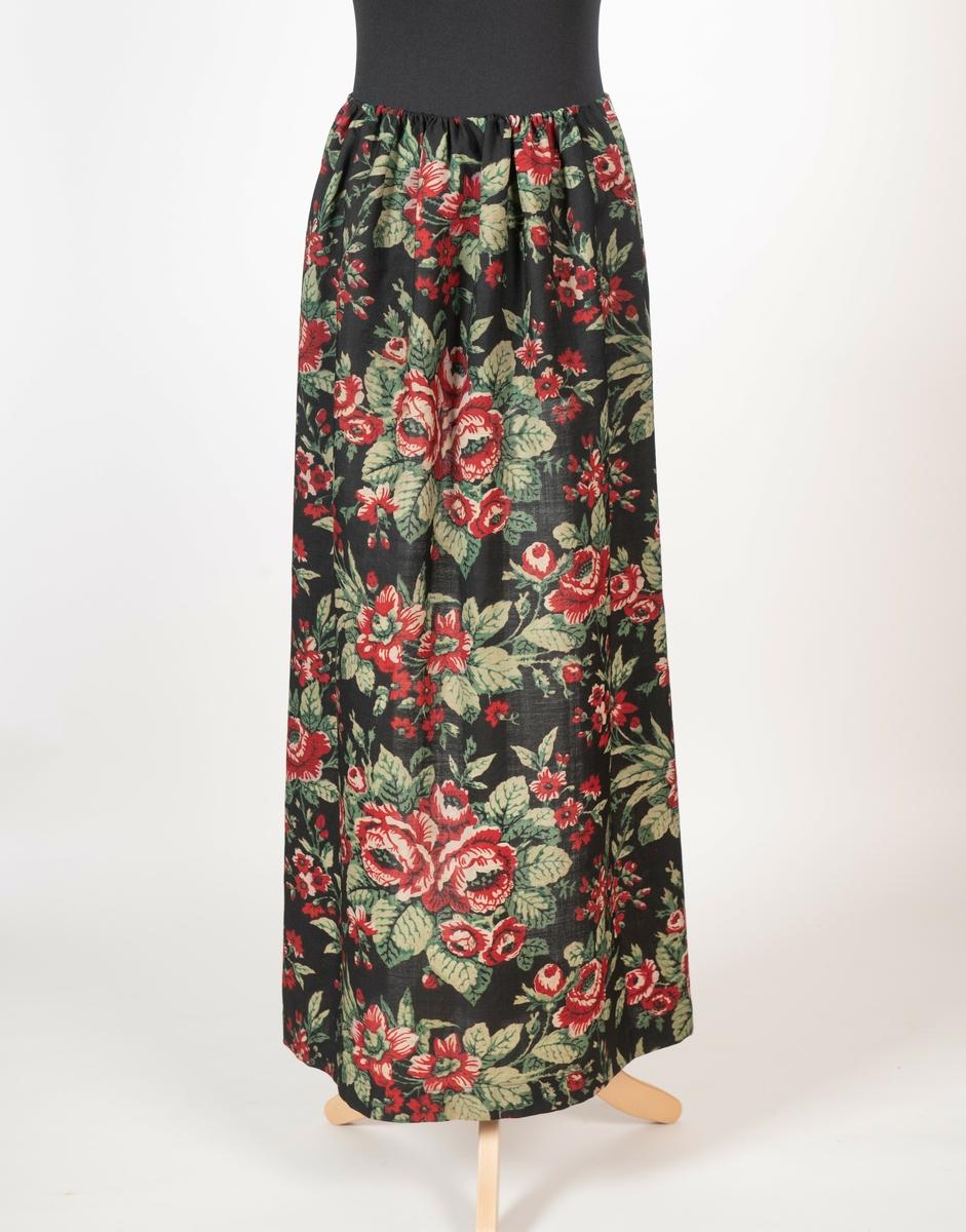 Forkle til folkedrakta for Sigdal-Eggedal. Sydd av sort ullmuselin med mønster av store roser og løvverk. Tvinnet forklesnor av grønn og sort bomull. Maskinsøm i folden.