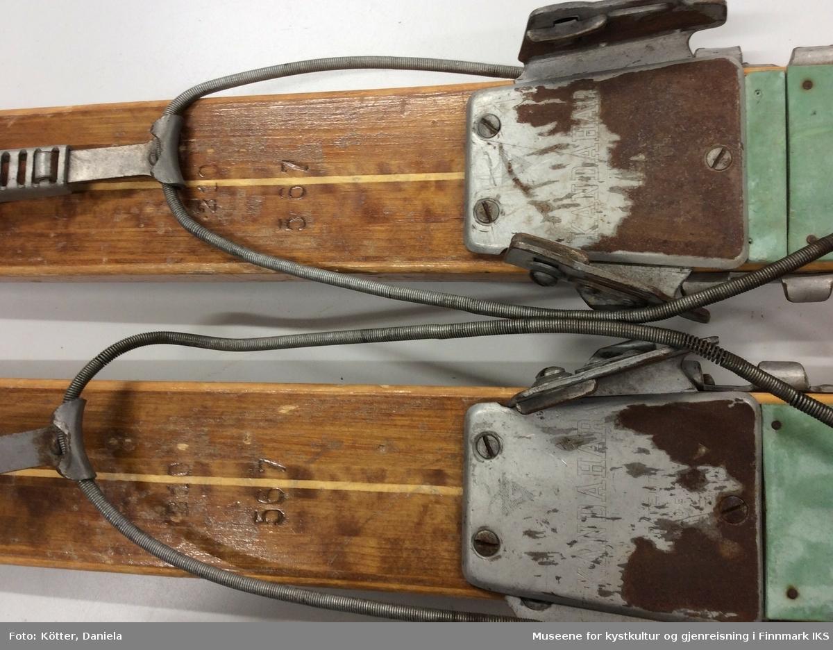 Tofarget treski med Kandaharbindinger. Skiene er mørke og har en lys stripe i midten. Helt foran på spissene er det påført firmalogoen til Madshus.  Bak bindingen er det spikret på biter av grønn linoleum eller kunststoff. Helt bak har skiene en metallkant. Foran bindingene er det slagmerker med tallene 210 og 567.