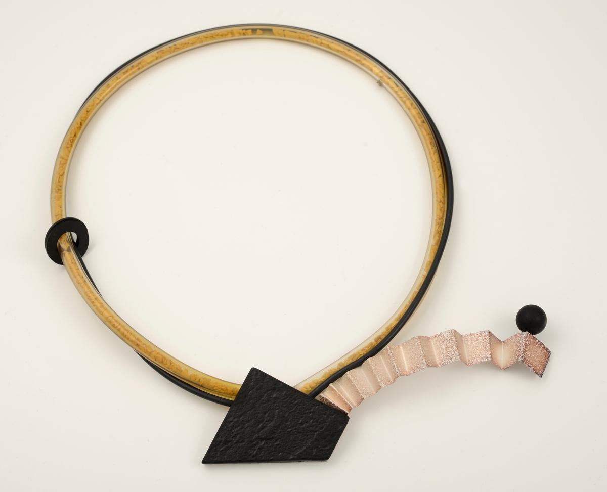 """Halssmykket består av en svart gummisnor og et tynt, blankt plastrør som er fylt med gule, trelignende """"gryn"""". To svarte gummiringer er tredd rundt snor og rør. Endene av disse er festet sammen i en ring til en uregelmessig, rektangulær plate. Platens bakside er av lyst metall, forsiden av svart plast. Et langt, foldet bånd av metall er festet til platen. En rund, svart plastkule er festet på enden av båndet.  Halssmykket oppbevares i en rektangulær eske som er kledd med blå fløyel og foret med gul skumplast."""