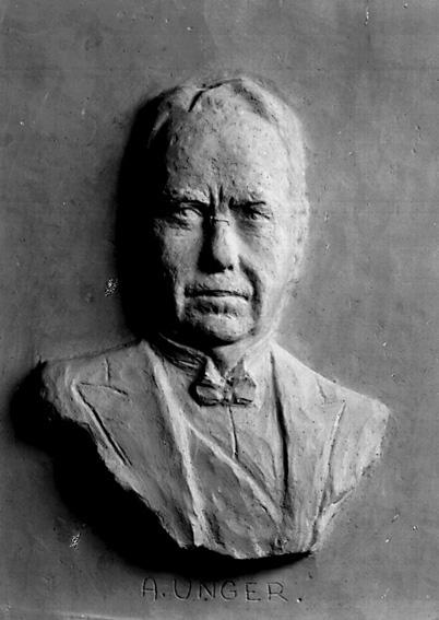 Relief av Abraham Unger; skulptör Sixten Nilsson.Sixten Nilsson (1911-1962), var verksam som skulptör, målare, grafiker och tecknare. Lärare i teckning och bildhuggeri vid Karlstads yrkesskola. Studerade vid Académi Scandinave i Paris för bland annat Despiau 1935, vid Konsthögskolan i Stockholm för Nils Sjögren 1936-40 och vid Escuela Superior de Bellas Artes de San Jorge i Barcelona 1952-53. Studieresor till Norge, Frankrike och Spanien. Han är främst representerad i Karlstad bland annat med bysten över K. M. W:s grundare G. A. Andersson på Hagatorget och på Värmlands museum.Källa: Svenskt konstnärslexikon, 1957.