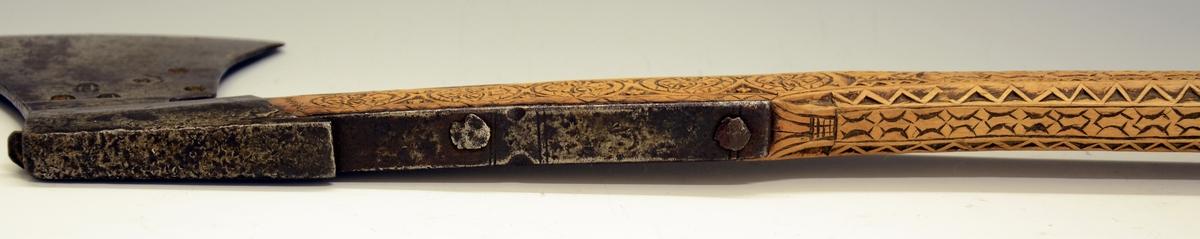 Håndøks. Bondeøks type C. Fra protokollen: Haandøks med originalt træskaft. Øksen har den sædvanlige utsvungne form. Falen går som en holk indover skaftet, og paa begge sider av dette er naglet i jernspenger som gaar ind i falen og holder øks og skaft sammen. Paa den ene side er øksen stemplet med 3 stjerner og 3 stempler i form av et skjold med A indi. Skaftet er ret, med endeholk og pigg, rikt utskaaret paa alle sider, fremme ved øksen 6 bladroser i kerbsnit og langs den smale del en eiendommelig ornamentkjede garnert med romaniserende zikzakborder, skurden er tilsvarende paa begge flatsider. (R. Berge)