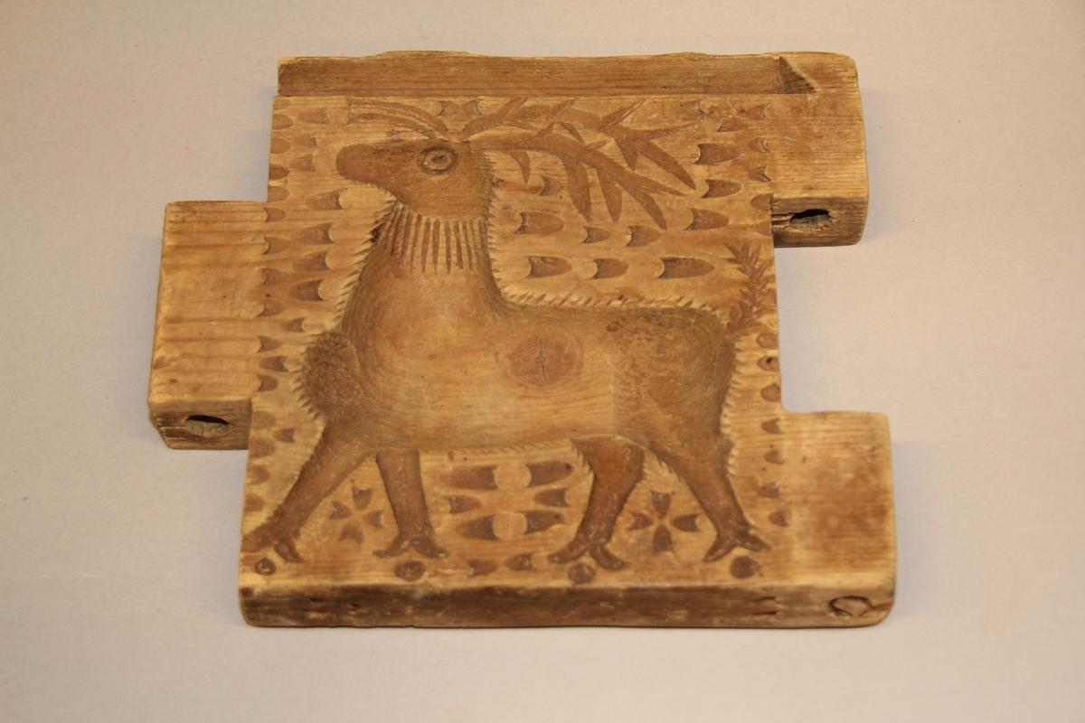 """Form av tre til smør eller ost. Forma er sett saman av fire trestykker som er ledda. Desse kan setjast saman til ein firkanta """"ring"""" . Trestykka er sett saman med trepinnar. Inni er forma dekorert med fint mønster i treskurd.Kvar side har ulikt mønster. ein hjort, ei løve, ein fugl og eit fabeldyr."""