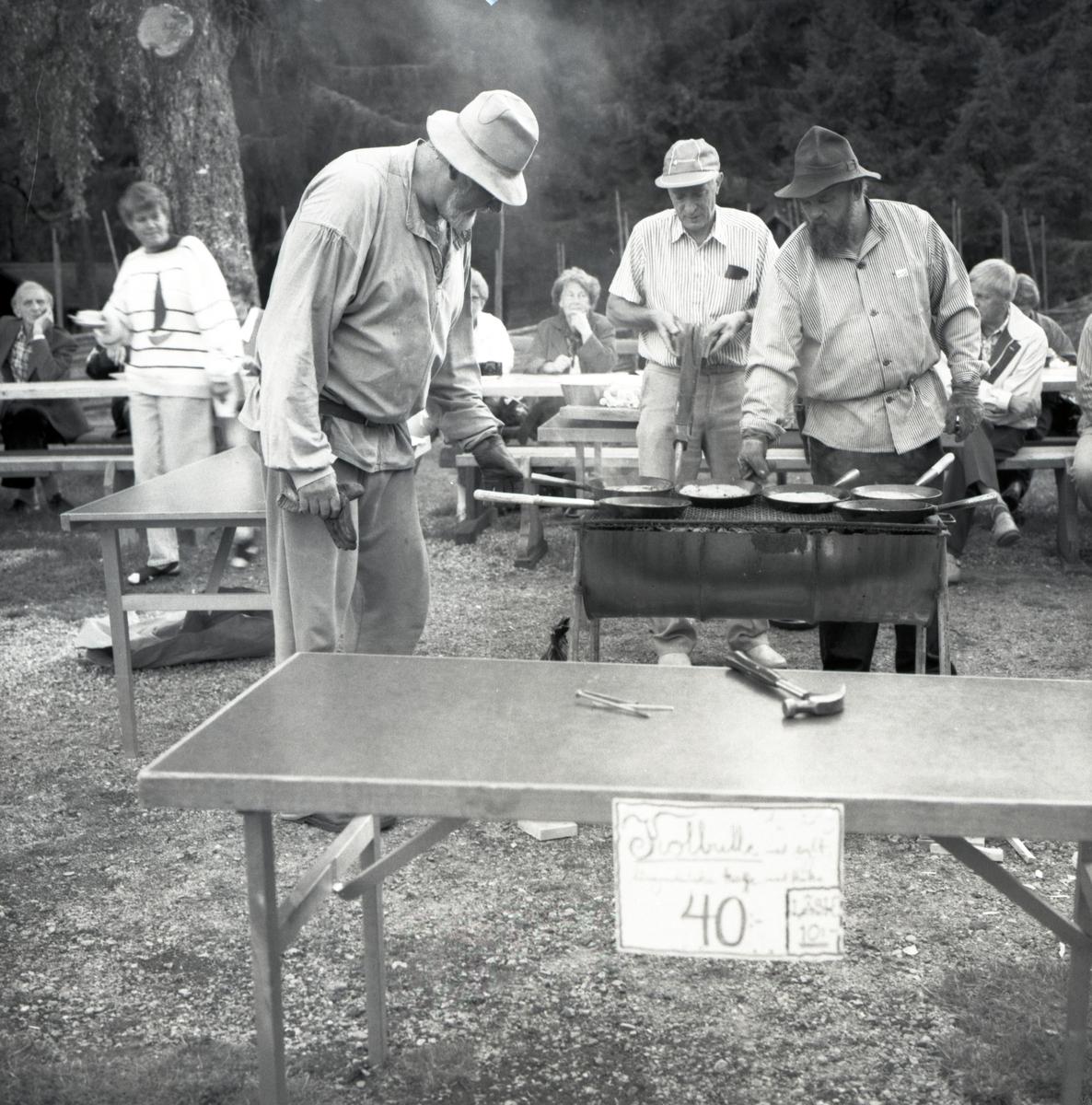 Två män gräddar kolbullar på en utegrill. En tredje underhåller glöden med blåsbälg. 1992.