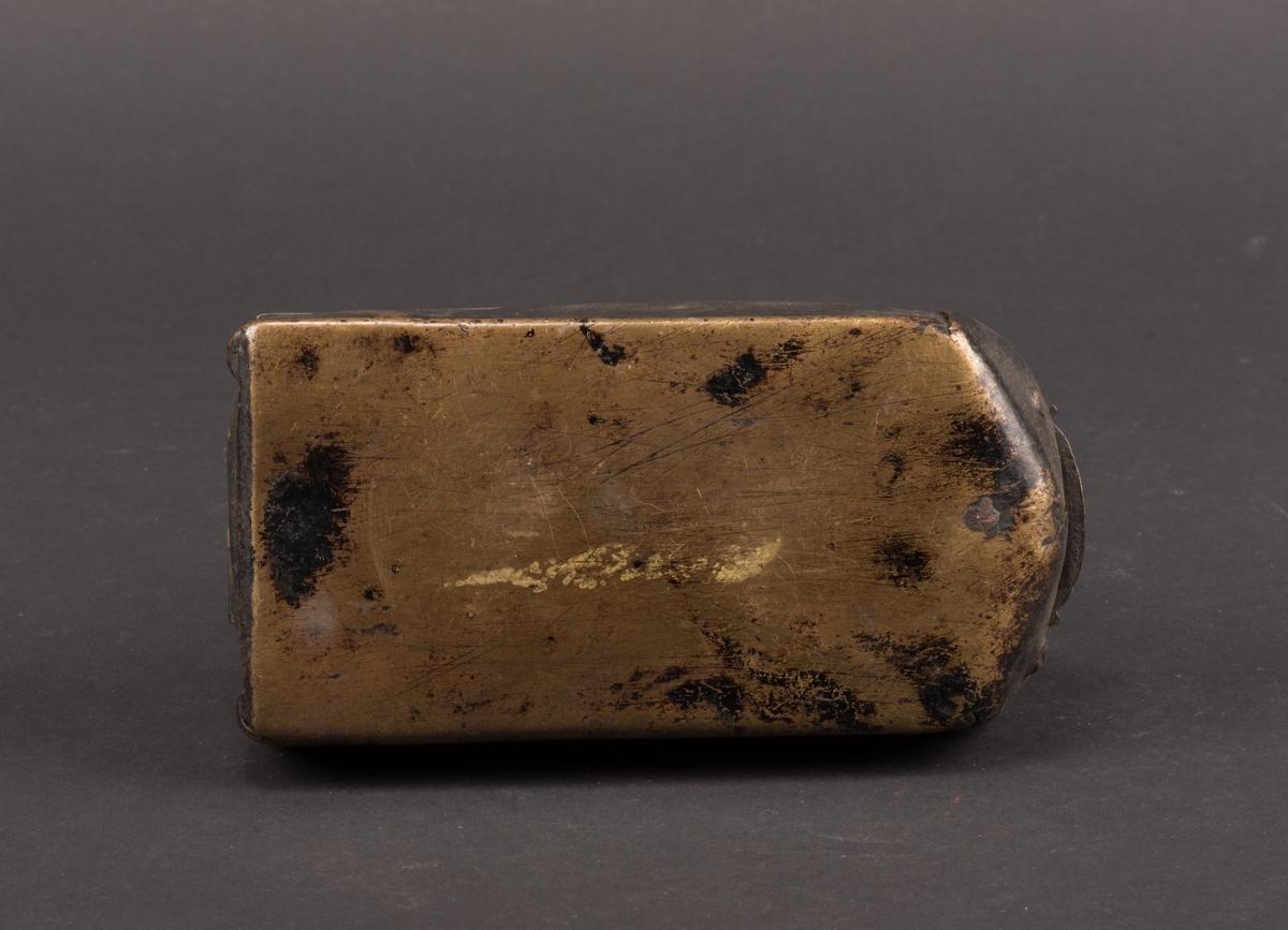 Strykjärn av mässingsplåt. Rektangulärt, något rundad framtill. Svarvat trähandtag som sitter i järnfästen. Strykjärnets överdel går att öppna och fungerar som lock. Locket är fäst med ett gångjärn, av järn, på insidans bakre del. För att låsa i stängt läge finns en böjd mässingssten. På ovansidan finns ett årtal, 1742, samt initialer, KAD, inristade.