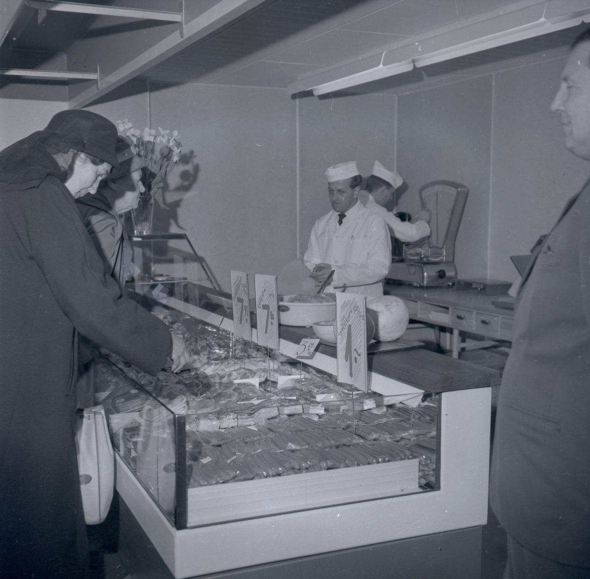 Bild tagen i samband med invigning av Konsum. Kvinnor som handlar kött samt personal i vita båtmössor och vita rockar.