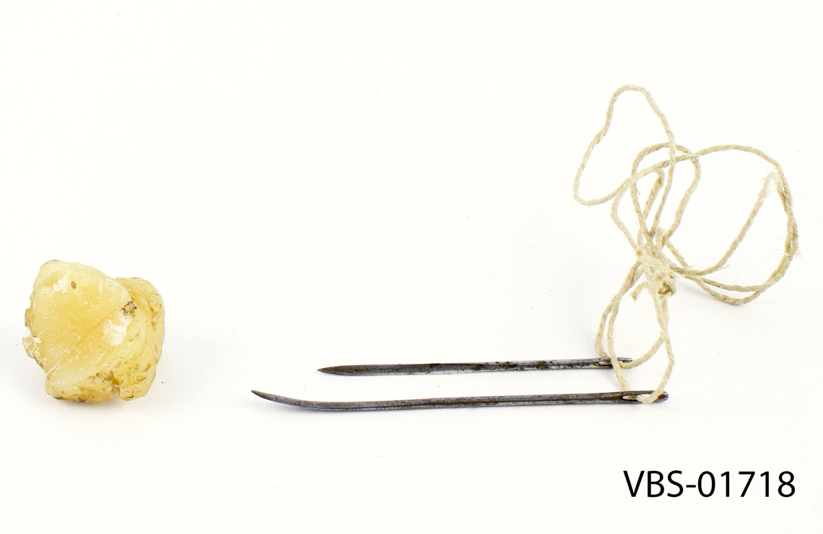"""To nåler i rustfritt stål, med trekantet seksjon. En av de to nåler er lengre, med en bredere og buet spiss. På den lille er det gravert """"Made in England"""". De to nålene er fastet sammen i en vokset bomullstråd. Ved siden av dem er et stearin stykke."""