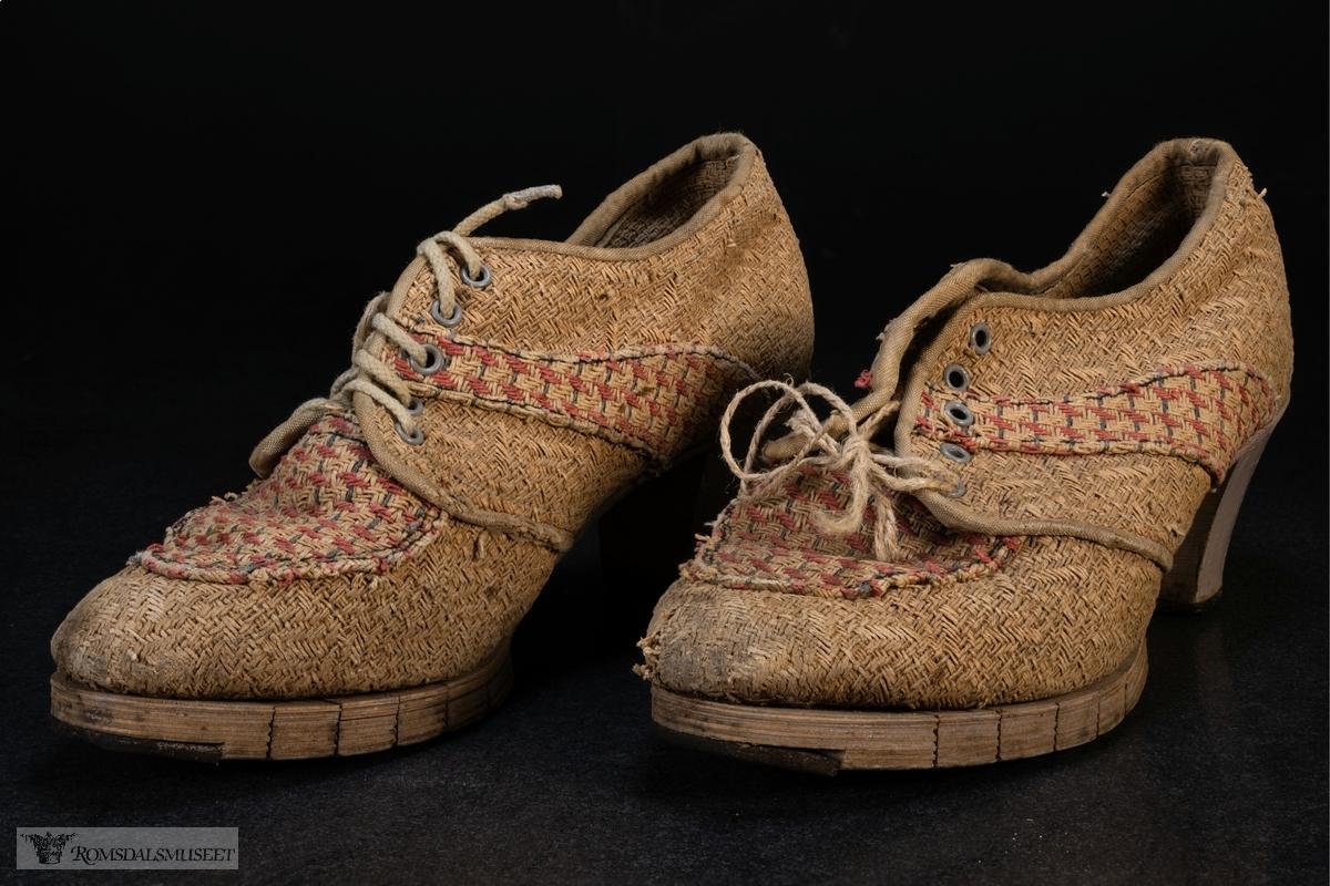 Høthelte sko med tykk hæl og oppdelt såle i front. Sidene og fronten har partier med rødt og grått mønster.