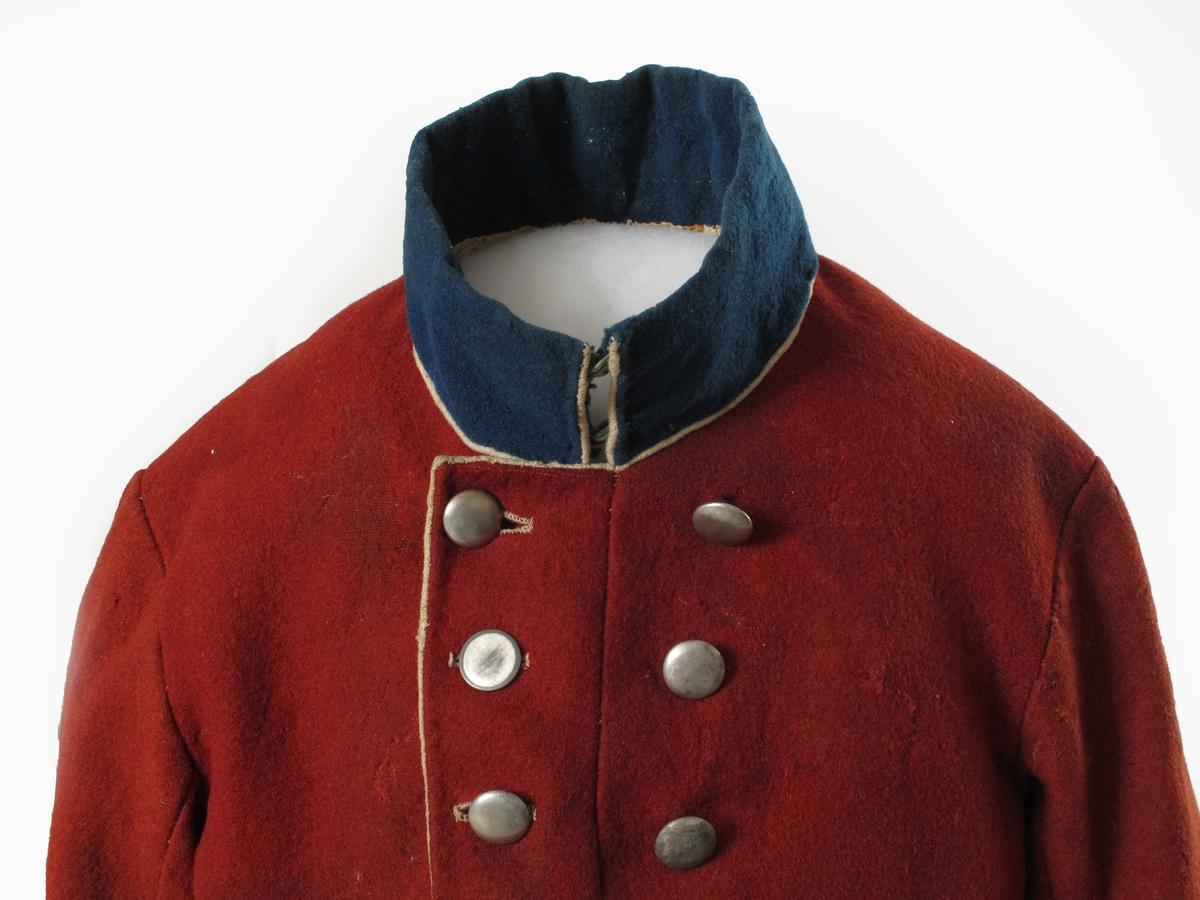 Uniform, kjolemodell 1842  for det danske infanteriet. Våpenkjole. Rødt tykt ullstoff, blå oppslag på mansjetter, med hvite passepoils. Høy blå opprettstående krave med hvit passepoil, fronten dobbeltknappet med 16 blanke tinnknapper, hvorav 1 mangler. Hvite knapphull, hvit passepoil langs åpningen foran. Figurskåret rygg med korte skjøter, med falske  lommeklaffer, skjøtene har bred, hvit kant og passepoils, klaffene hvite passepoils. Hvitt lerretsfor, skjøtene foret med grovt hvitt ullstoff. Stoppinnlegg i brystet. Tilstand nov. 1959: Møllspist, muggflekket.