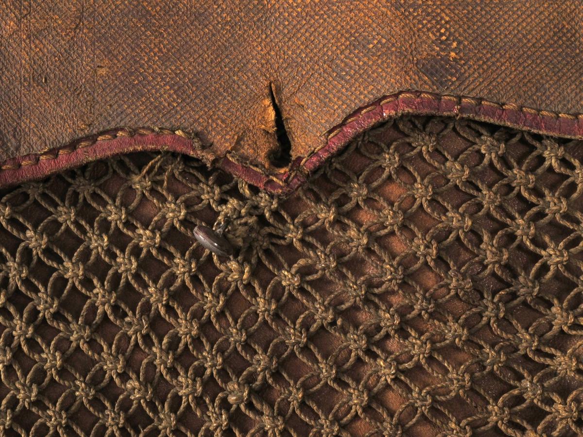 """Jakttaske.av brunt lær,  kantet med rødt, knyttet forstykke av seilgarn. Flat, rundbunnet pose  av lær med tre indre små rom og et stort, lukkes med klaff med  tunget  kontur, med rødt skinnbånd, tettskravert, opprinnelig sort  lær. Bare  en av to små runde knapper er bevart. Over forstykket et  """"nett"""" av  brunt seilgarn, knyttet i forskjellig mønster, langs kantene  lange,  tette frynser av samme garn.  Tilstand: svært skitten, antag. p.g.a. lagring i AAM."""