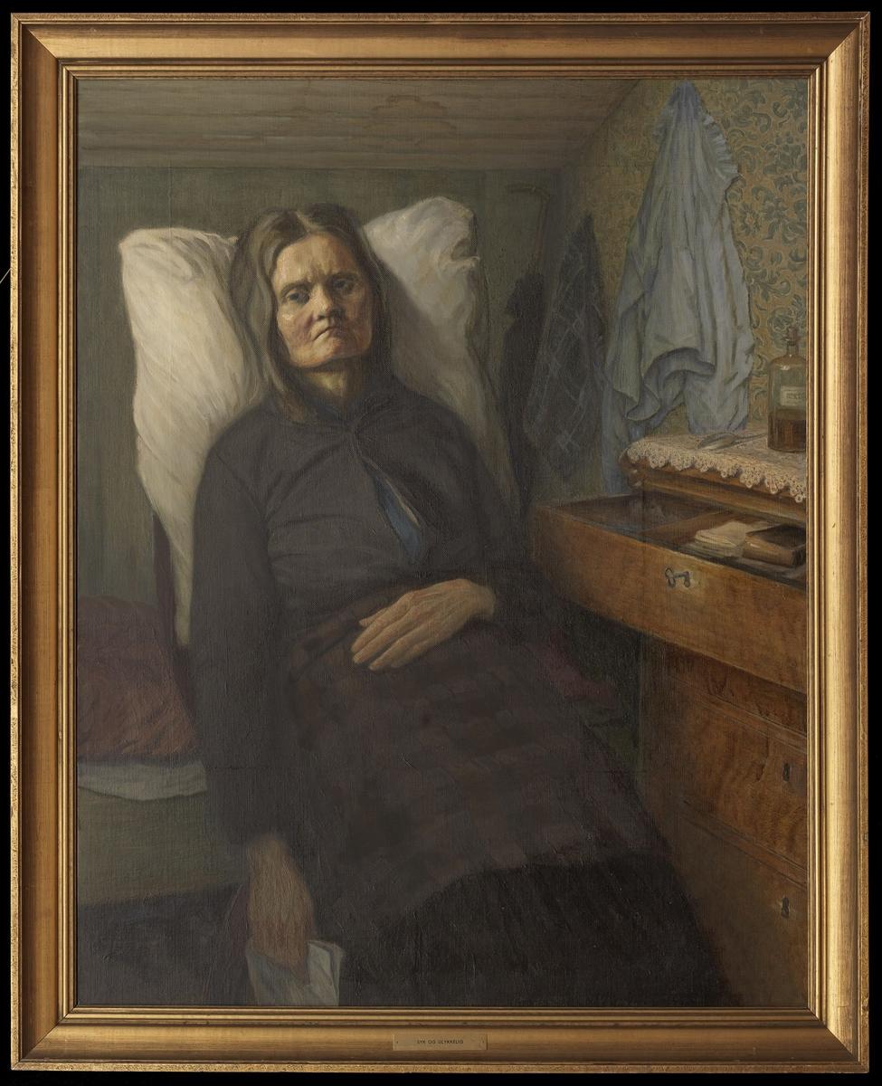 Kvinne i interiør, sittende, noe høyrev., knestk., hvit pute bak, løst hår, mørk blågrå drakt, gul kommode
