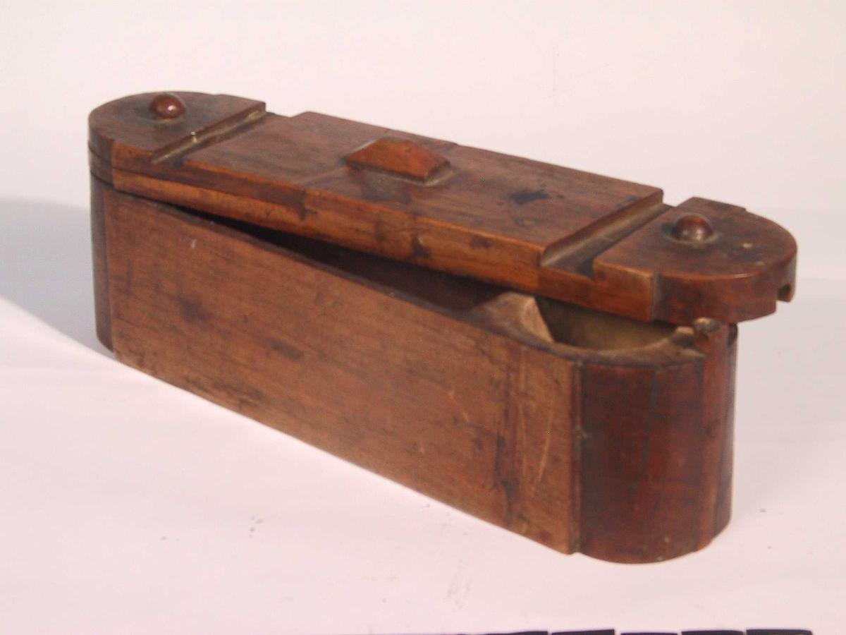 """Rettsidet  skrin med   rundede kortsider, skyvbart lokk  som er festet i den ene kortende. Lokket har en fast, """"valmet"""" knott pm,  lokket skyves fra i 2 omganger. Innvendig et rom og et rektangulært.  Tilstand: god. Skyvelist i den kortende hvor lokket er festet er borte.   I skrinet lå:   b) Barberkost i tinnhylse, kost med gul bust skrus inn i hylsen. Kost L.  6,6. Hylse L. 6,6. Di. 2,5. Med hvelvet lokk., L. sammenslått 7,3    c) Barberkniv, 1920-30-årene. Stål med sort bakelittskaft, stålet stemplet:  """"5 Jahre Garantie"""" og """"Solingen"""" L. 23,4.    d) Redskap av stål. L. 5,7 St. B. 2,5. To kuler i spenn i en bøyle."""