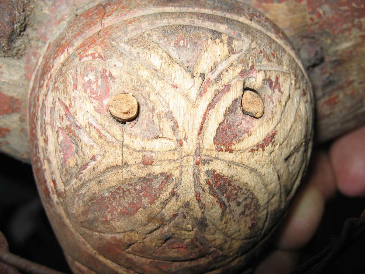 """Høvre av tre kronet med løvefigur. Den ene høvreballen mangler. Mellom tømmeringer av stål er det strukket en ståltråd (har neppe vært der fra begynnelsen). På begge sider er det et hull i treet for feste av bukgjord, på den ene siden også en smidd """"øyeskrue"""". Flotte sammenføyninger med kiler og tapper."""