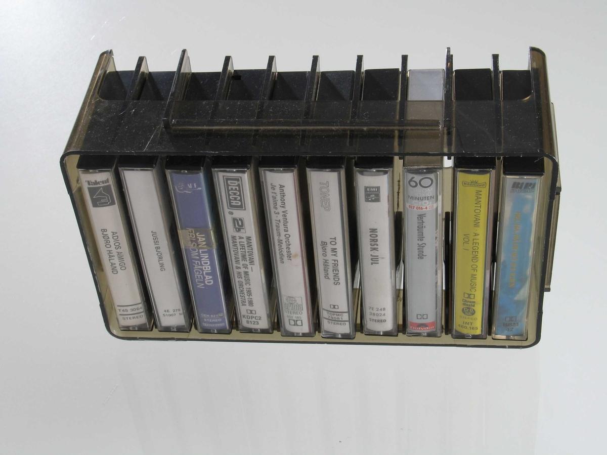Form: Rektangulær kasse med avrunda hjørner, med plass til 10 kassetter