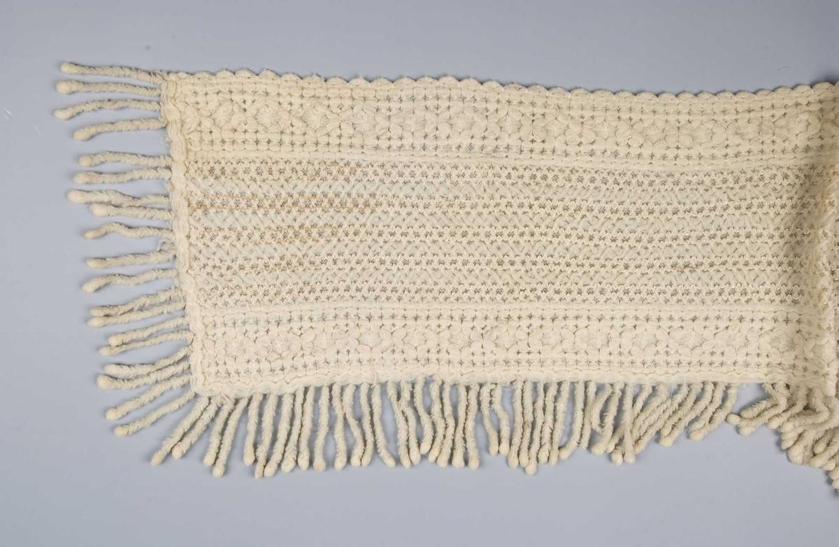 Hvitt ullsjal som er dobbelt med mønstret forside og glatt forside med frynser på 3 kanter. Noen tynne blanke tråder danner mønster (usikkert materiale)
