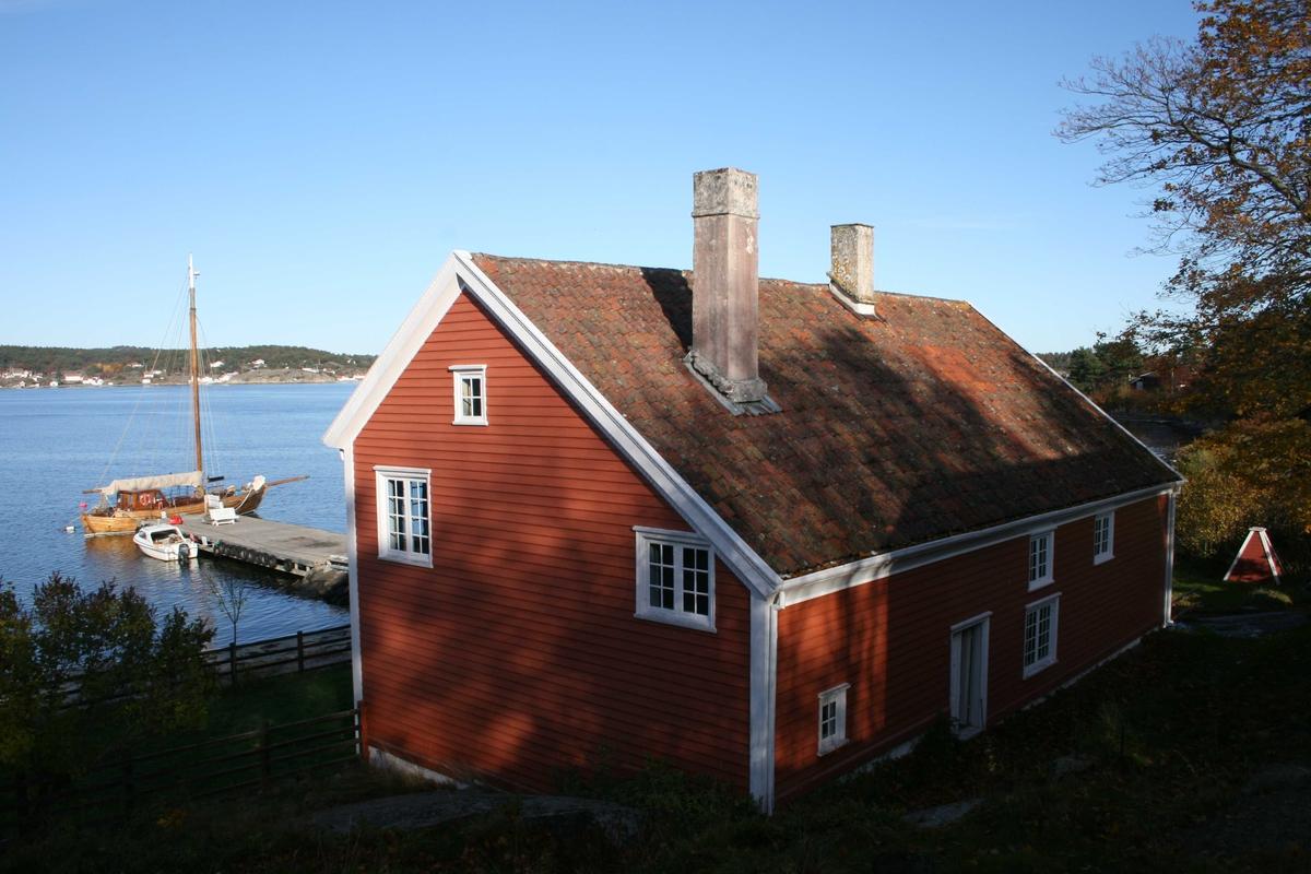 Merdøgaard, gårdstun, sett fra V. Våningshusets gavl mot vest, Revesandsfjorden i bakgr.