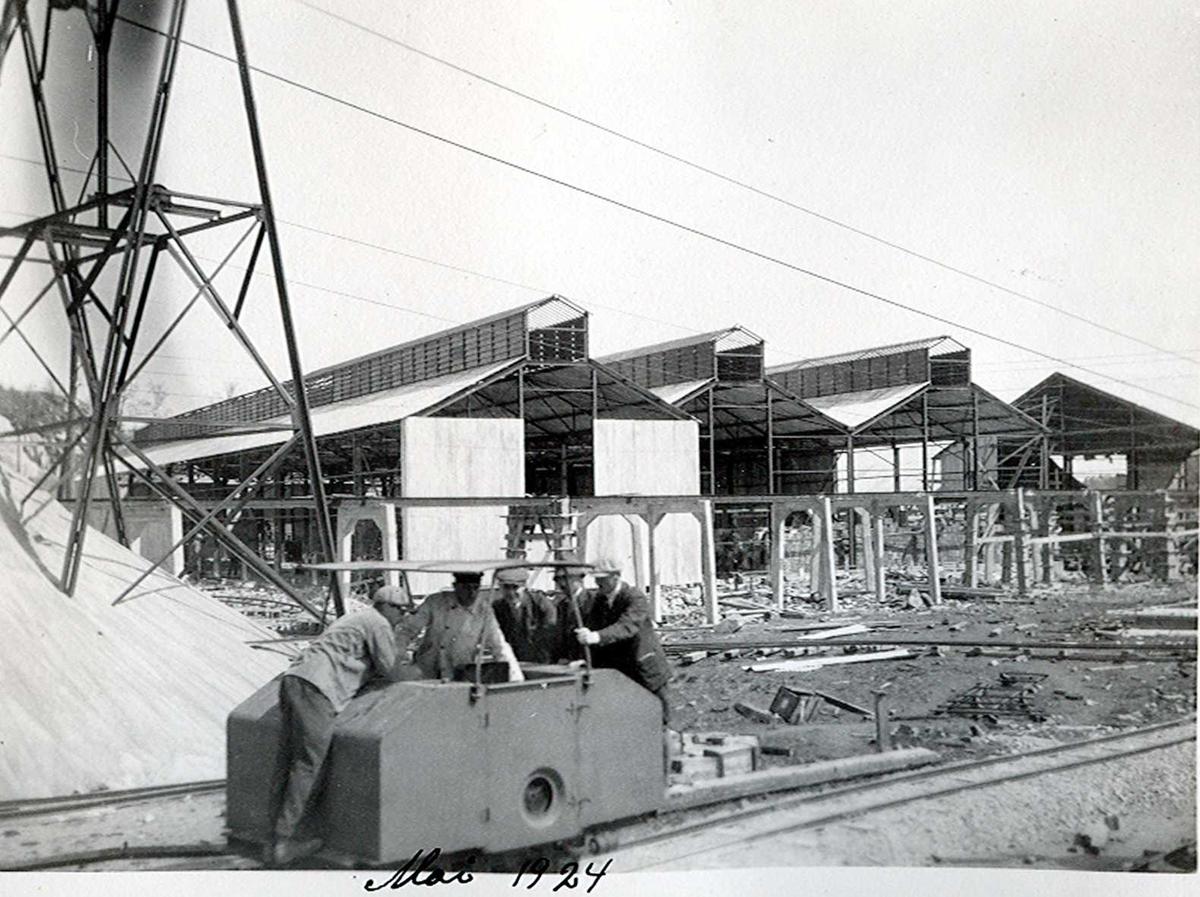 """""""xx/05-1924"""" Nitriden. Bygninger for steking av elektrodekull. Skinnegang, """"høybanen"""", sees foran bygningene. I forgrunnen kjøres et dieseldrevet lokomotiv. Taubanemast til venstre og dagdeponi for bauxitt. Taubanevogn tømmes i det øyeblikk foto tas. Kaianlegg til høyre."""