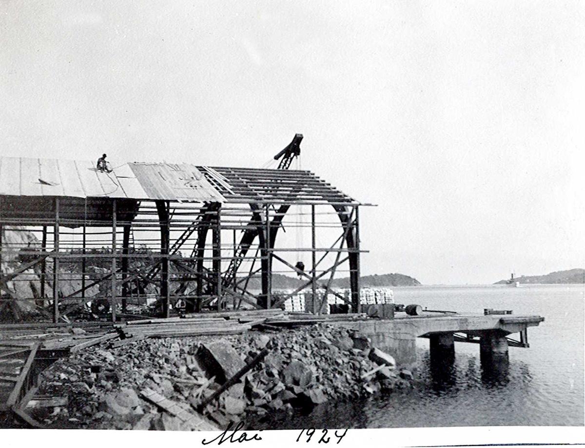 """""""xx/05-1924"""" Nitriden. Stålkonstruksjoner for lagerbygning, østre kai. Skinnegang. Tromøysund og Tromøy til høyre. Hvideberget i bakgrunnen. En av kystens """"hvite svaner"""" (rutebåter) på vei vestover i Tromøysund."""