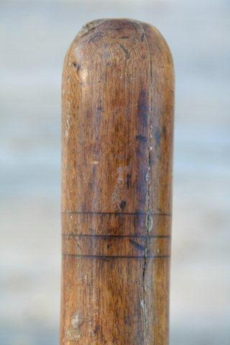 Flatt, bredt jern med skrå egg. Tange med firkantet tverrsnitt. Holk.  2 striper rundt nedre og 3 striper rundt øvre del av skaft.