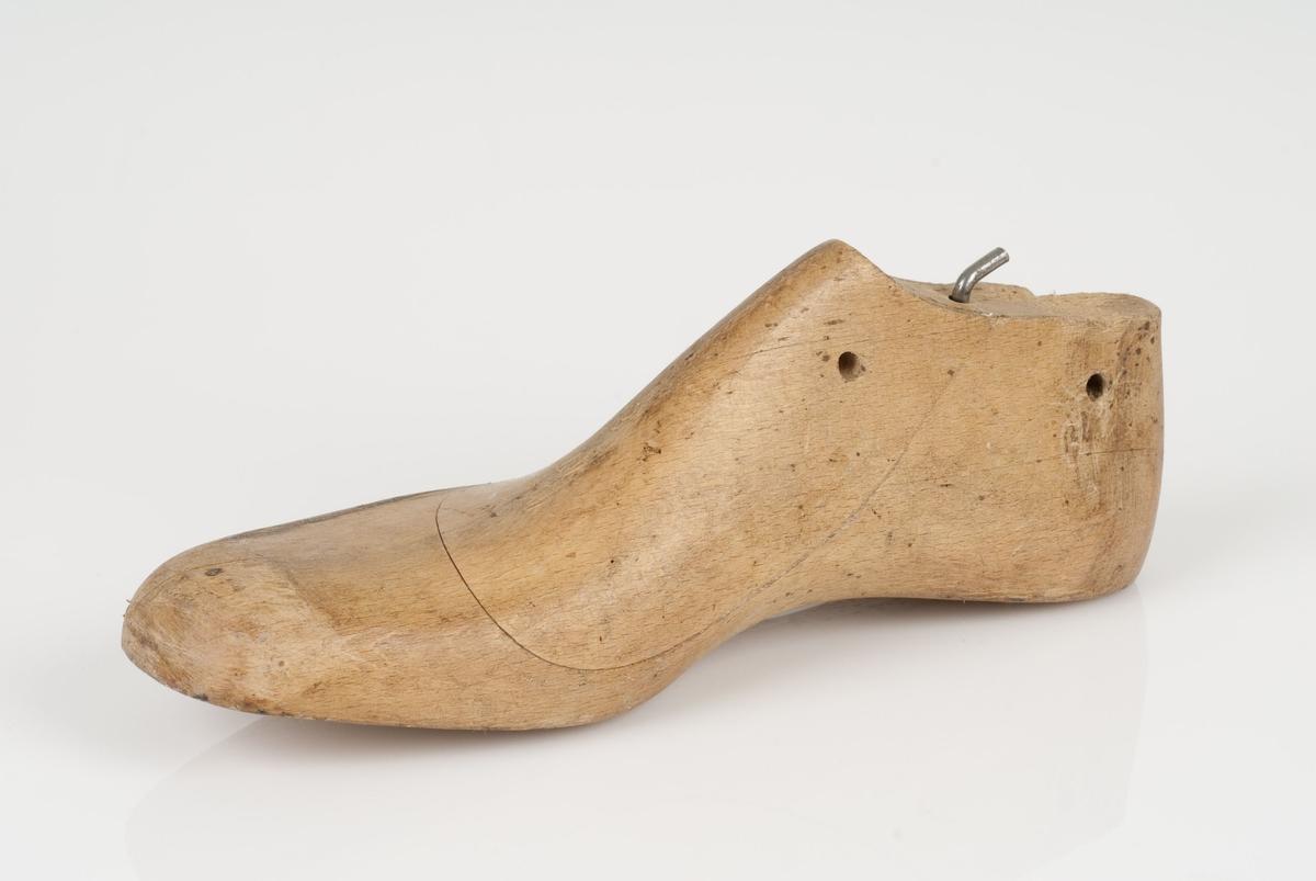 En tremodell i to deler; lest og opplest/overlest (kile). Høyrefot i skostørrelse 47, og 8 cm i vidde. Skrue som holder fast kile og lest.