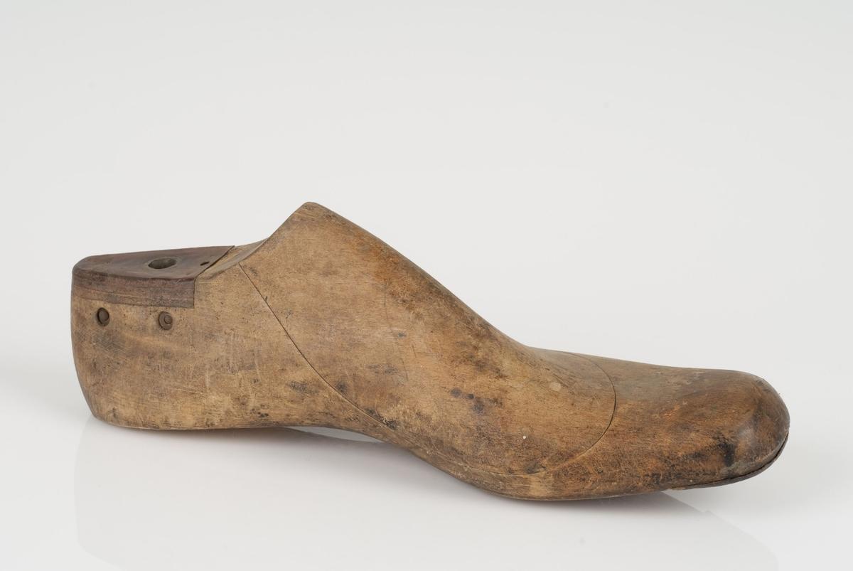 En tremodell i to deler; lest og opplest/overlest (kile). Venstrefot i skostørrelse 47, og 8 cm i vidde. Lestekam i skinn.