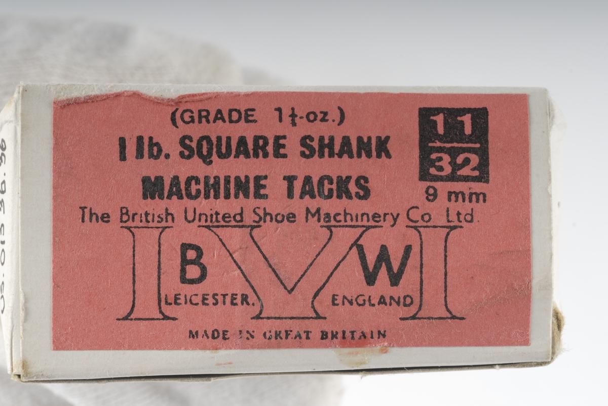 En eske som inneholder spiker av stål. Esken er hvit med en rosa påklistret lapp med sort påført tekst på bunnen.