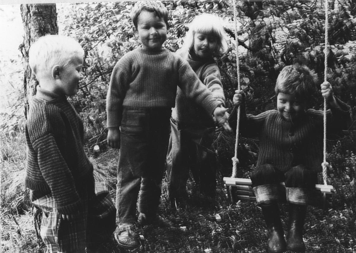 Fire barn ved en huske.