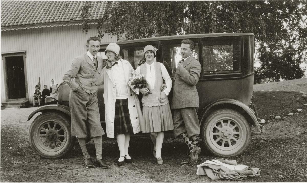 To yngre damer og to menn står inntil bil. Tre personer i bakgrunnen sitter i husveggen.