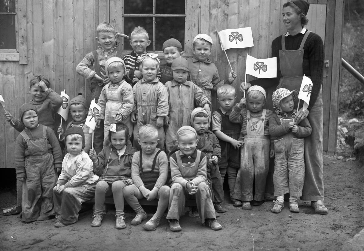 Gruppe barn – og en voksen. Skilt med NKS – Norske Kvinners Sanitetsforening. Barnehage?