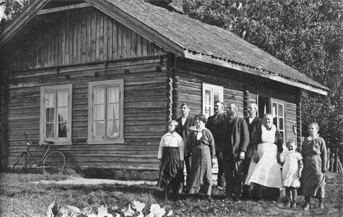 Barn og voksne utenfor et tømmerhus. Olava Vardrum.